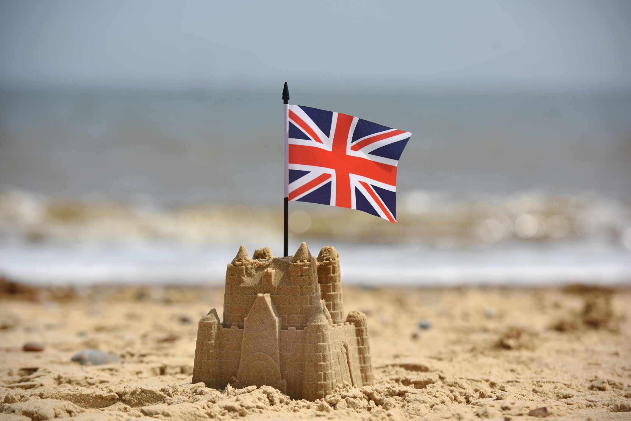 A lone sandcastle on an English sandy beach with a British Union Jack flag.